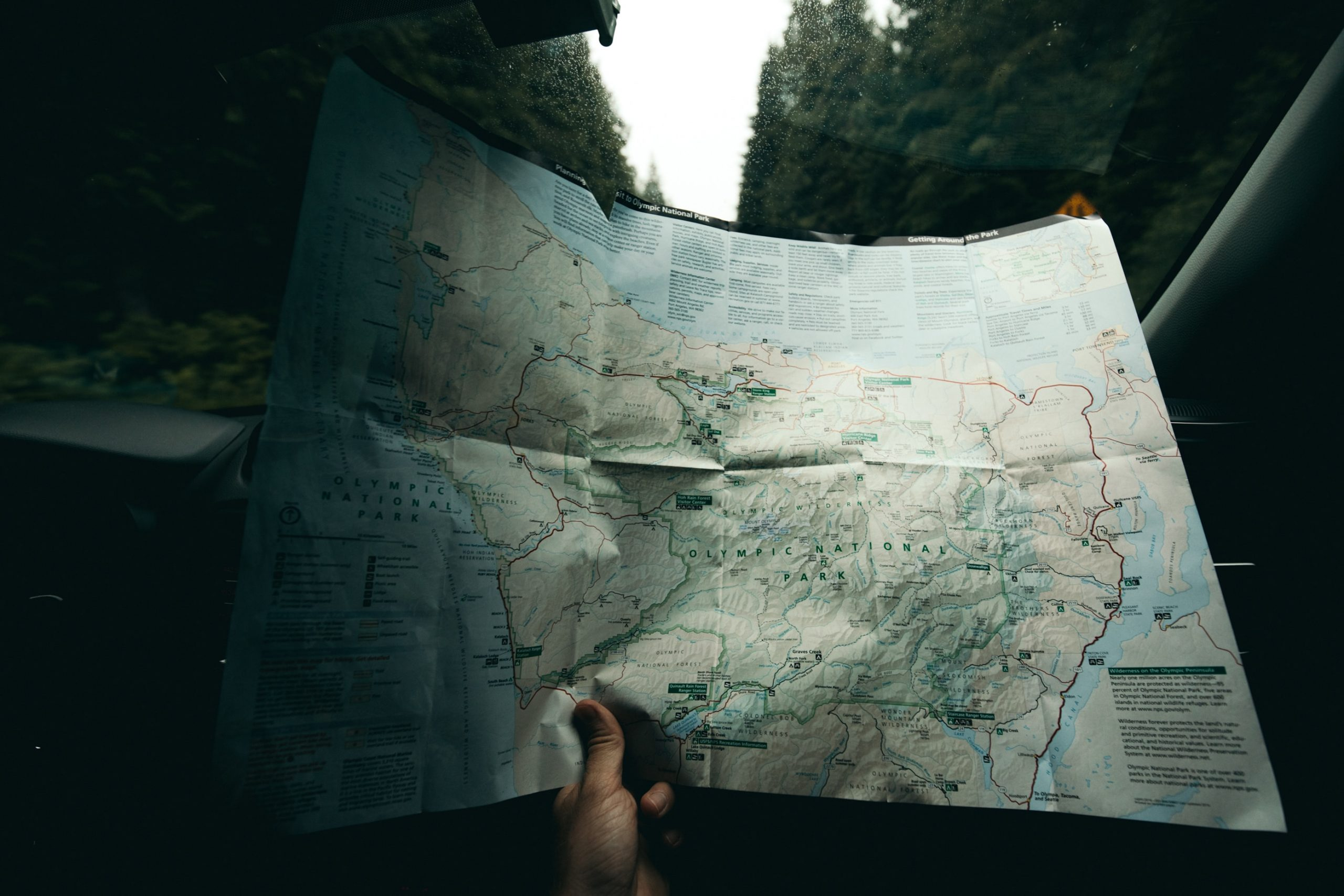 Excellent.Org: a hand is holding a map of the olympic national park