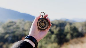 Excellent.org explains the best leadership style for success, the picture shows a hand holding a compass