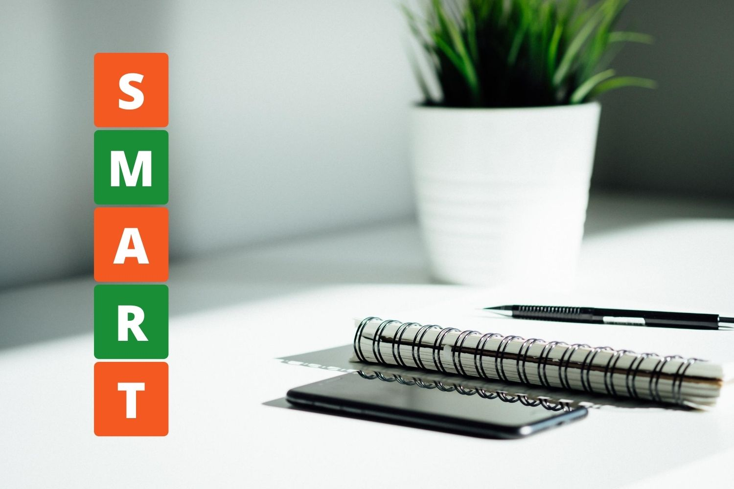 Excellent.org explains how to set and achieve better goals with the SMART method, the picture shows a notebook and smartphone on a table, on the picture is the word SMART